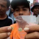 Warga memperlihatkan koin emas (mata uang Dirham) yang ditemukan di kawasan tambak Desa Merduati, Kecamatan Kutaraja, Banda Aceh, Selasa (12/11) Koin emas kuno yang diperkirakan berjumlah ribuan itu pertama kali ditemukan dalam sebuah peti kuno oleh seorang pencari tiram dan dijual ke toko emas di Pasar Atjeh hingga seratusan juta Rupiah. SERAMBI/BUDI FATRIA